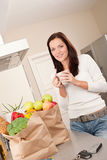 Woman with groceries in the kitchen Stock Image