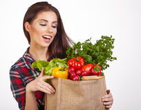 Woman with groceries shopping bag full of healthy vegetables smi Royalty Free Stock Photos