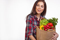 Woman with groceries shopping bag full of healthy vegetables smi Royalty Free Stock Images