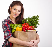 Woman with groceries shopping bag full of healthy vegetables smi Royalty Free Stock Photo