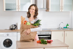 Woman With Grocery Bag In Kitchen Stock Images