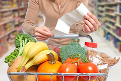Woman with grocery receipt and shopping cart. Woman with grocery shopping cart of food over abstract background Stock Photo