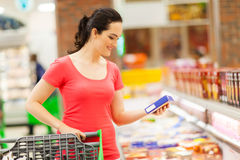 Woman grocery shopping. Young woman doing grocery shopping in supermarket Stock Photos
