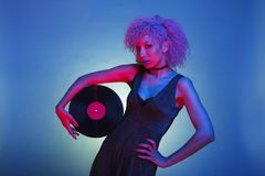 Woman with groovy hair holding an old vinyl with pink and blue royalty free stock photo