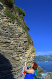 Woman and ground layers,Adriatic coast. Adult tourist woman taking photo of picturesque cliff layers and scenic view of Budva bay stock image