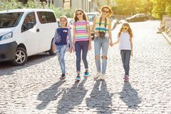 Woman with a group of children is laughing, walking around the city. Background of the European city, summer weekend, vacation, tourism Stock Photo