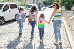 Woman with a group of children is laughing, walking around the city. Background of the European city, summer weekend, vacation, tourism Stock Images