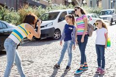 Woman with a group of children is laughing, walking around the city. royalty free stock images