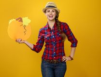 Woman grower on yellow background showing copy space pumpkin Stock Photo