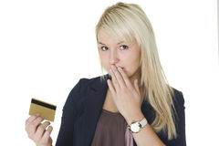 Woman with guilty look holding credit card Stock Photo