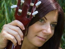 A woman and a guitar. Attractive middle-aged woman's face Royalty Free Stock Photos