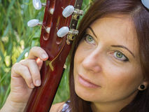 A woman and a guitar. Attractive middle-aged woman's face and the acoustic guitar parts Stock Photo