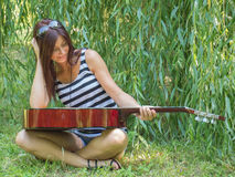 A woman and a guitar. Beautiful woman sitting on the green grass with a guitar Stock Image