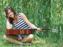 A woman and a guitar. Beautiful woman sitting on the green grass with a guitar and laughing Royalty Free Stock Photos