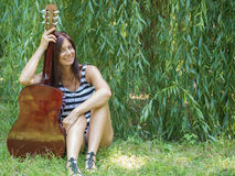 A woman and a guitar. Beautiful thin woman sitting on the grass with a guitar and laughing Royalty Free Stock Image