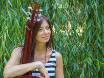 A woman and a guitar. Beautiful thin woman sitting before the willow tree with an acoustic guitar parts Royalty Free Stock Photo