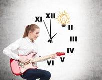 Woman with guitar and a clock Stock Photos