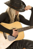 Woman with guitar and cowboy hat sit Stock Image