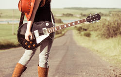 Woman with guitar at freeway Stock Photography