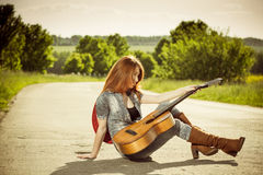 Woman with guitar at freeway Stock Photo