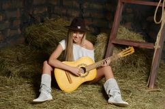 The woman with guitar on hay Royalty Free Stock Images