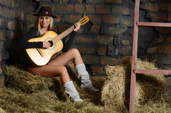 The woman with guitar on hay Royalty Free Stock Image