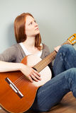 Woman with a guitar at home Stock Image