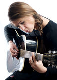 Woman Guitar Musician. A woman with a braid plays guitar in front of a white background very focused Royalty Free Stock Photos