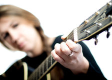 Woman Guitar Musician Hand. Close up on the hand of a guitar-playing woman with her in the background Stock Photo