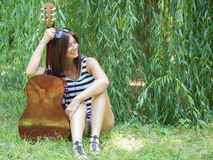 A woman, a guitar and a nature. Beautiful thin woman sitting on the grass with a guitar and laughing Royalty Free Stock Images