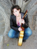 Woman With Guitar Outdoors. Female musician sitting at the base of a tree--soft focus and glow of color Stock Photo