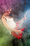 Woman with guitar playing hard-rock. Royalty Free Stock Photography