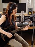 Woman with guitar in a recording studio royalty free stock photo