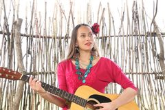 Woman with a guitar and a red rose in her hair stock photography