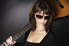 Woman with guitar on shoulders. Stock Photos