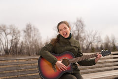 Woman with a guitar showing her tongue. She is sitting on a wooden bench outside stock image