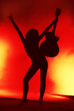 Woman with guitar silhouette on red background Royalty Free Stock Photography