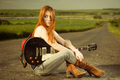 Woman with guitar sitting at asphalt Royalty Free Stock Photos