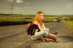Woman with guitar sitting at asphalt Stock Images
