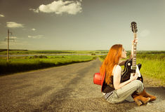 Woman with guitar sitting at asphalt Royalty Free Stock Images