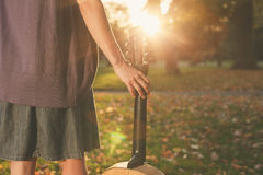 Woman with guitar at sunset in park Stock Photography