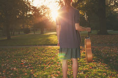 Woman with guitar at sunset in the park Royalty Free Stock Photos
