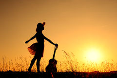 Woman and guitar with sunset silhouette Royalty Free Stock Photos