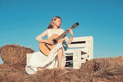Woman guitarist perform music concert. Sensual woman play guitar on wooden bench. Fashion musician in white dress on. Sunny nature. Albino girl hold acoustic stock photography