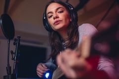Guitarist playing guitar in a recording studio. Woman guitarist playing guitar in a recording studio. Female singer singing a song in studio Royalty Free Stock Photo