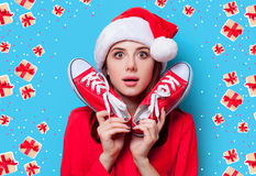 Woman with gumshoes. Portrait of a young redhead woman in Santa Claus hat with gumshoes on blue background Stock Images