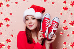 Woman with gumshoes. Portrait of a young redhead woman in Santa Claus hat with red gumshoes on pink background Stock Photo