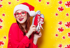 Woman with gumshoes. Portrait of a young redhead woman in Santa Claus hat and with gumshoes on yellow background Royalty Free Stock Photo