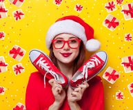 Woman with gumshoes. Portrait of a young redhead woman in Santa Claus hat and with gumshoes on yellow background Stock Image