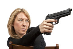 Woman with gun. A blond woman directing her pistol towards someone as she is sitting on a chair stock photo